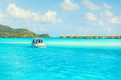 Blue turquoise lagoon and small boat on far bungalows background Stock Image