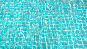 Blue turquoise refreshing water aqua on swimming pool surface. Waves and wind at tropical morning. Blue turquoise bright refreshing water aqua on swimming pool stock video footage