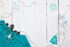 Blue, turquoise sweater on a white wooden background with new-year decorations. Blue, turquoise sweater on a white wooden background with New Year decorations stock images