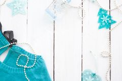 Blue, turquoise sweater on a white wooden background with new-year decorations. Blue, turquoise sweater on a white wooden background with New Year decorations royalty free stock photo