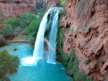 Blue turquoise waterfall on red travertine Stock Images
