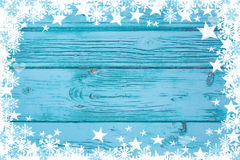 Blue or turquoise wood background for advertising or a greeting. Card with stars and snowflakes Royalty Free Stock Photo