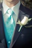 Blue Tuxedo Neck Tie. White tuxedo shirt collar, blue printed necktie, vest and black jacket. flower on lapel Royalty Free Stock Images