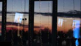 Blue tv screens reflected on big decorated windows. Picture of beautiful red sunset is behind the glass. Blue tv screens reflected  on big decorated windows stock video footage