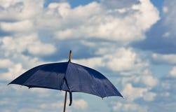 Blue umbrella against a cloudy sky. The blue umbrella against a cloudy sky stock image