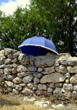 Blue umbrella on ancient wall of ruins of Acinipo Royalty Free Stock Photos