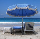 Blue umbrella and deckchairs Stock Photos
