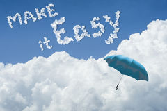 Blue umbrella floating above against Blue sky and cloud.Sunny day.Cloudscape.close up the cloud.text make it easy.make it easy. Concept.easy life in new year Stock Photo
