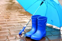 Blue umbrella and gumboots. On wet pavement Stock Photos