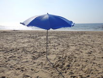Blue umbrella isolated on a sandy beach with blue sea background. On a beautiful summer day blue umbrella standing in the sand background blue sea Royalty Free Stock Photography