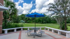 Blue umbrella and metal steel table of the cafeteria of a state college in Florida, USA stock photos