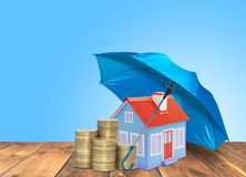 Umbrella protection House coins savings a business. Protection money insurance home concept. Blue umbrella protection House coins savings a business. Protection Royalty Free Stock Photo