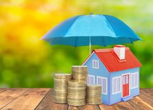 Umbrella protection House coins savings a business. Protection money insurance home concept. Blue umbrella protection House coins savings a business. Protection Stock Photography