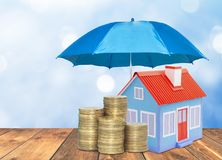 Umbrella protection House coins savings a business. Protection money insurance home concept. Blue umbrella protection House coins savings a business. Protection Royalty Free Stock Images