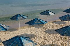 Blue umbrellas. At an empty beach in Bulgaria Stock Images