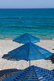 Blue umbrellas on a beach Royalty Free Stock Photos
