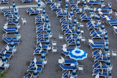 Blue umbrellas and chaise longue on empty sandy beach, Amalfi, Italy Royalty Free Stock Image