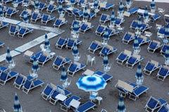 Blue umbrellas and chaise longue on empty sandy beach, Amalfi, Italy Royalty Free Stock Photos