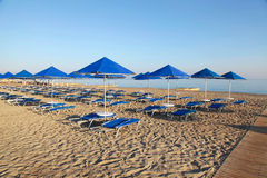 Blue umbrellas and chaise longue on empty sandy beach, Greece Royalty Free Stock Photography