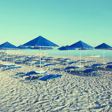 Blue umbrellas and chaise longue on empty sandy beach, Greece Stock Images
