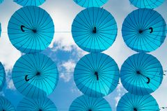 Blue umbrellas float in sky on sunny day. Umbrella sky project installation. Holiday and festival celebration. Shade and. Protection. Outdoor art design and stock images