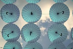 Blue umbrellas float in sky on sunny day. Umbrella sky project installation. Holiday and festival celebration. Shade and. Protection. Outdoor art design and royalty free stock images