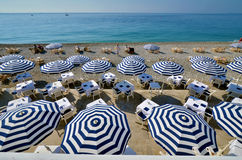 Blue umbrellas. Mediterranean beach with striped blue umbrellas Royalty Free Stock Images