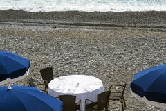 Blue umbrellas, reserved tables with white tablecloths on the pebble beach of the Promenade des Anglais in Nice, France, await gue. Sts. Cozy restaurant on the stock images