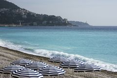 Blue umbrellas, reserved tables with white tablecloths on the pebble beach of the Promenade des Anglais in Nice, France, await gue royalty free stock photos