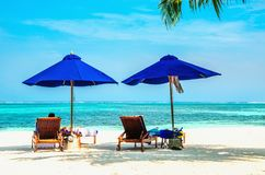 Blue umbrellas and wooden couches on a sandy beach. Wit azure water Stock Photography