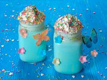 Blue unicorn hot chocolate with whipped cream, sugar and sprinkles. Blue unicorn hot chocolate with whipped cream, sugar and colorful sprinkles, set on a blue Royalty Free Stock Photo