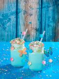 Blue unicorn hot chocolate with whipped cream, sugar and sprinkles. Blue unicorn hot chocolate with whipped cream, sugar and colorful sprinkles set on a blue Stock Photos
