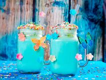 Blue unicorn hot chocolate with whipped cream, sugar and sprinkles. Set on a blue wooden board Royalty Free Stock Image