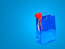 Blue Valentines Day holiday gift bag and red heart on blue backg Stock Photos