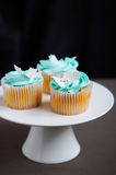 Blue vanilla cupcakes on stand Royalty Free Stock Images