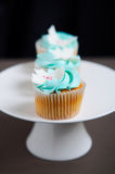 Blue vanilla cupcakes on stand Stock Photo