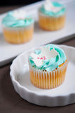 Blue vanilla cupcakes on stand Stock Image