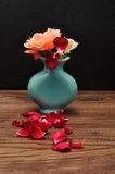 A blue vase with rose where one has lost its petals Royalty Free Stock Photography