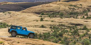 Blue vehicle on a rugged terrain in Moab, Utah. Two people inside a blue vehicle are braving the rough terrain in Moab, Utah on a sunny day. The scenic rocky royalty free stock photos