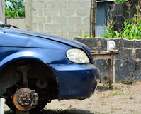 Blue Vehicle Under repair. Suspended with a jack and cement clock and its front tire pulled out for reach to its alternator belts stock photography