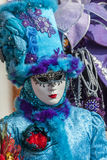 Blue Venetian Disguise. Venice,Italy-February 18, 2012: Environmental portrait of a person wearing a mask and a specific blue disguise in Venice during the Royalty Free Stock Images
