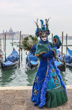 Blue Venetian Disguise. Venice, Italy- February 19, 2012: A person disguised in a beautiful blue disguise holding a mirror pose in San Marco Square in front of stock photo