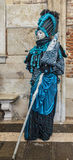 Blue Venetian Disguise. Venice,Italy- March 2, 2014: Unidentified person disguised in a blue costume with a scepter poses near the wall of The Doge's Palace in Stock Image