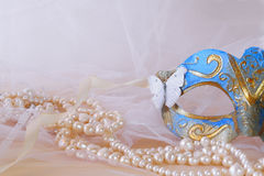 blue venetian mask next to pearls Royalty Free Stock Images