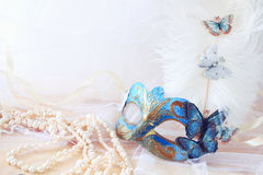 blue venetian mask next to pearls Stock Photos