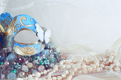 blue venetian mask next to pearls Stock Image