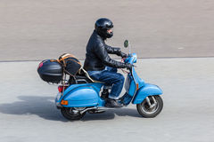 Blue Vespa scooter on the road Stock Photography