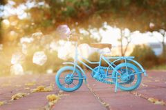 Blue vintage bicycle toy waiting outdoors at sunset light. Blue vintage bicycle toy waiting outdoors at sunset light stock images
