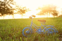Blue vintage bicycle toy waiting outdoors at sunset light. Blue vintage bicycle toy waiting outdoors at sunset light royalty free stock photos