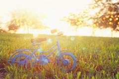 Blue vintage bicycle toy waiting outdoors at sunset light. Blue vintage bicycle toy waiting outdoors at sunset light stock photo
